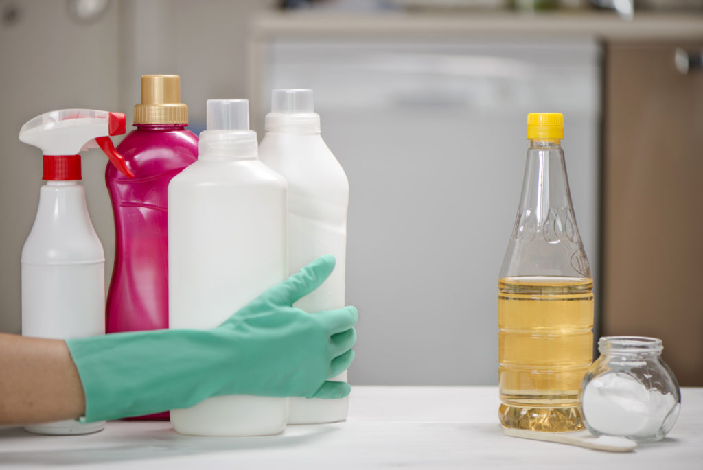 Hand moves chemical cleaners from table while letting vinegar remain.