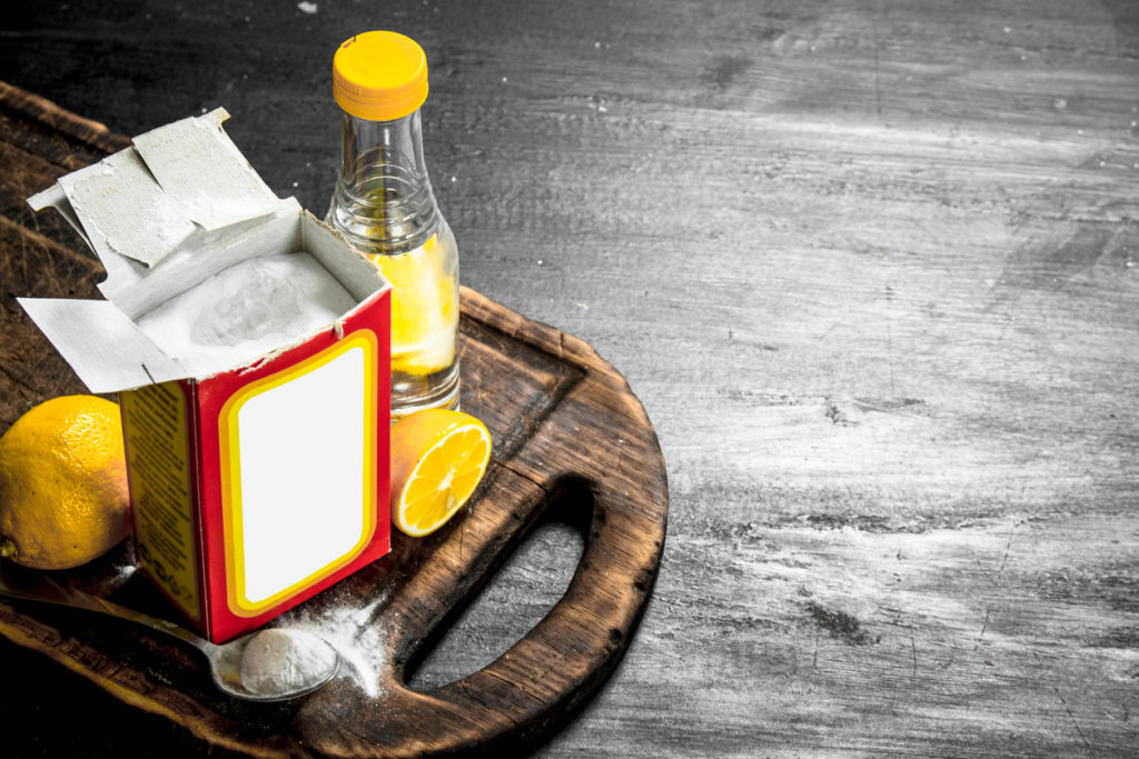Baking soda with vinegar and lemon. on wooden chopping board.