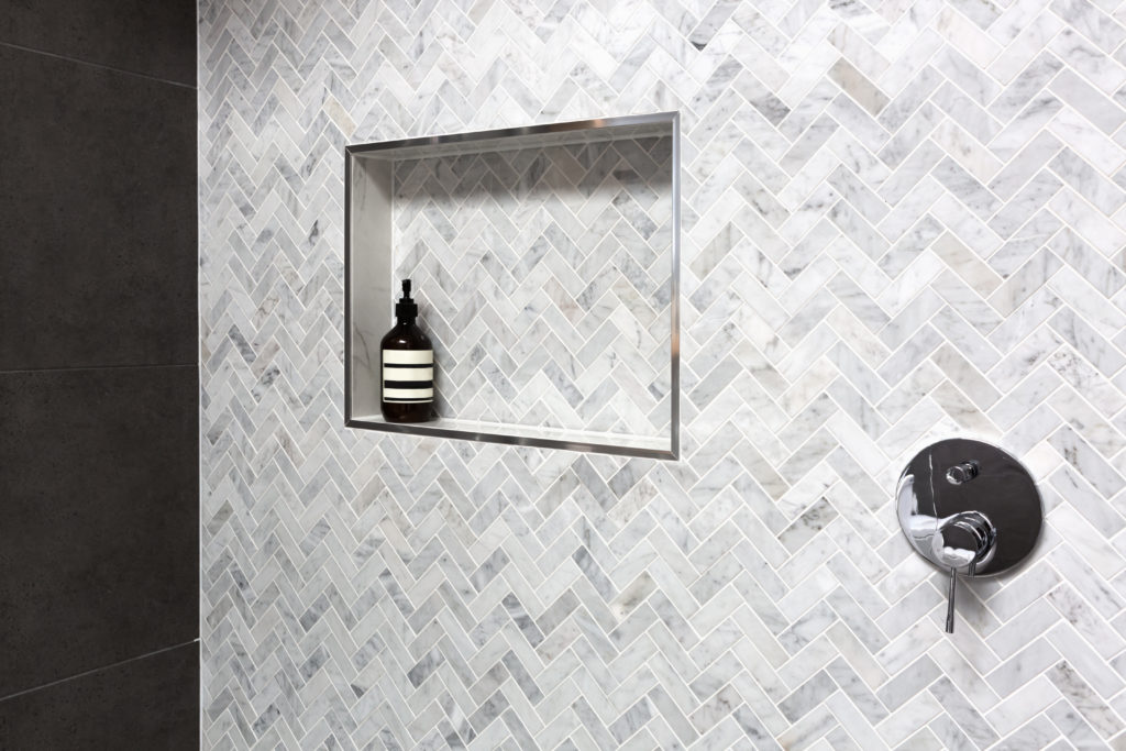Shower shelf detail in wall of herringbone marble tiles