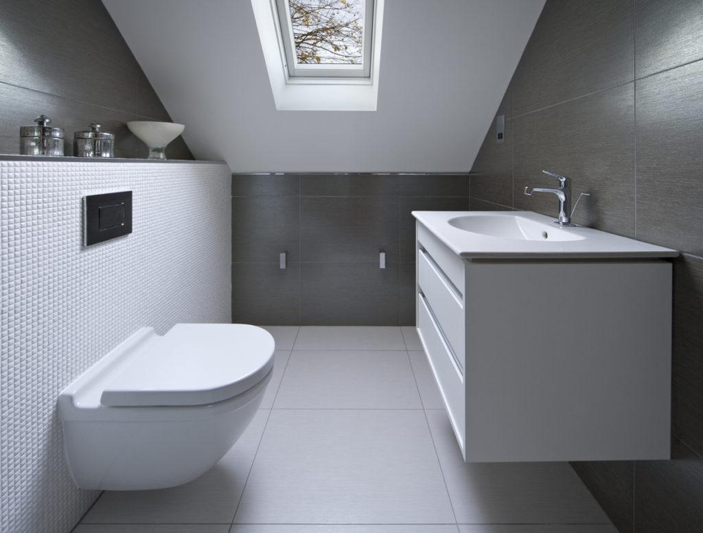 Monochrome attic bathroom with mounted furniture
