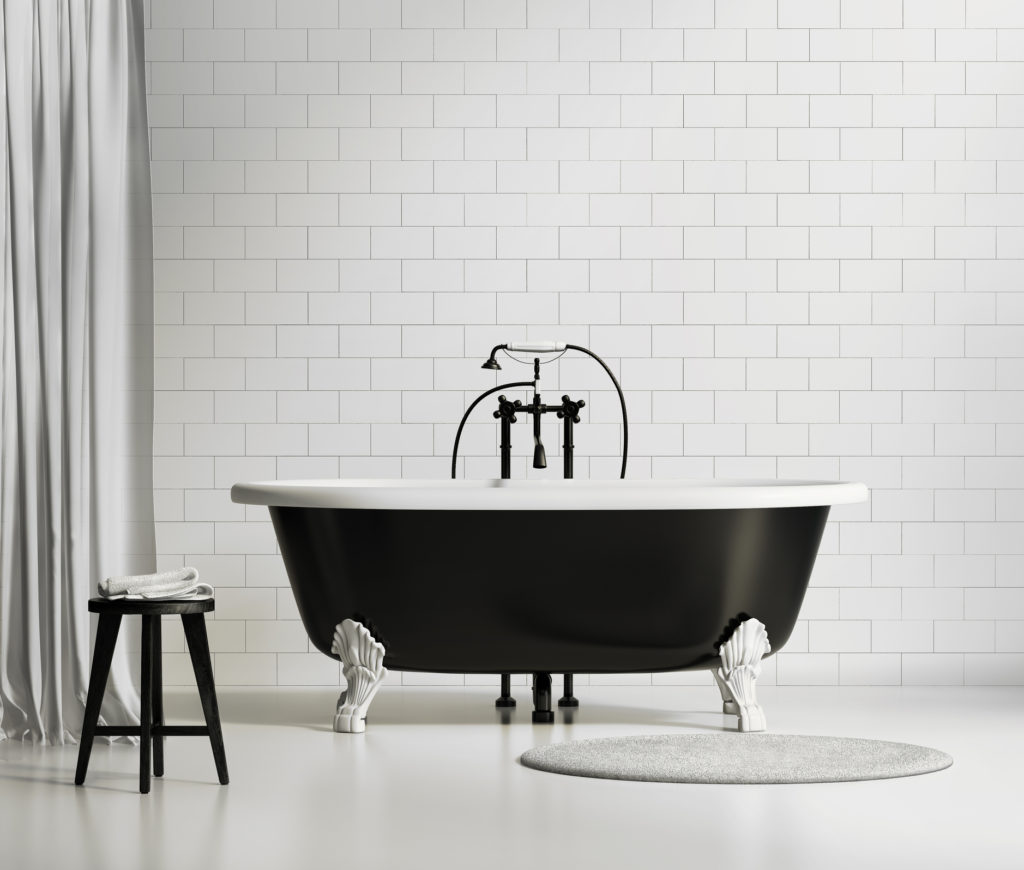 Classic black freestanding bath set against a white wall.